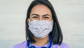 Latina woman wearing a covid mask. Blue headphones around her neck.
